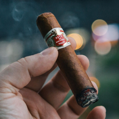 holding lit cigar